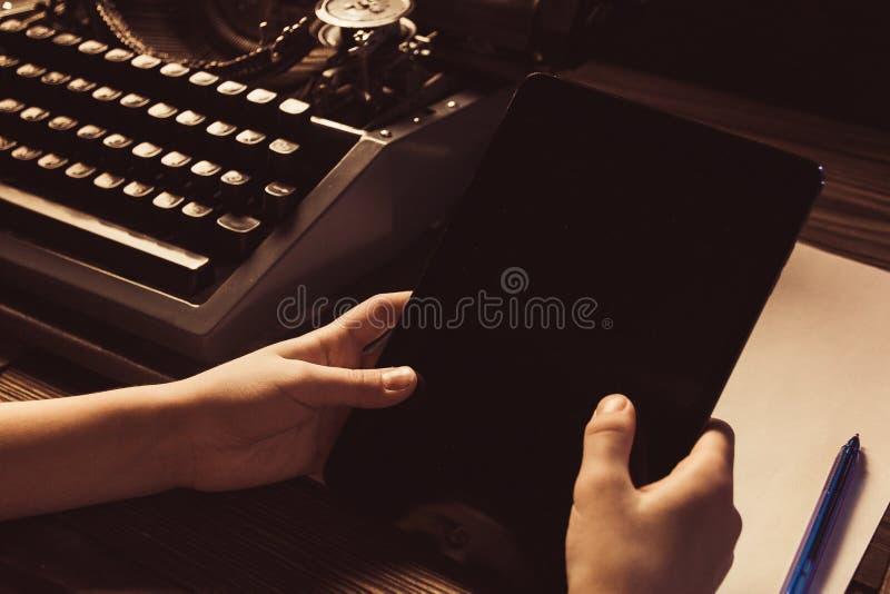 Skrivmaskin och en modern grej i händer ny teknik royaltyfri bild