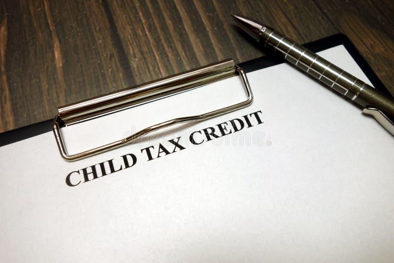 Skrivplatta med barnskattelättnadmodellen och penna på skrivbordet arkivfoton