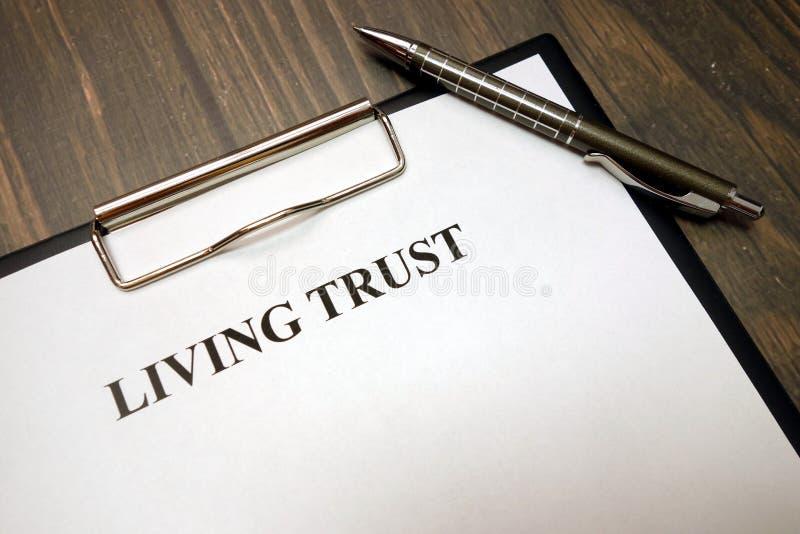 Skrivplatta med bo förtroende och penna på skrivbordet royaltyfri fotografi