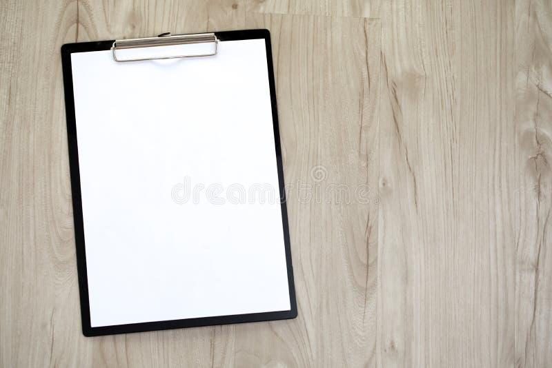 Skrivplatta med ett tomt ark av papper på trätabellen royaltyfri bild