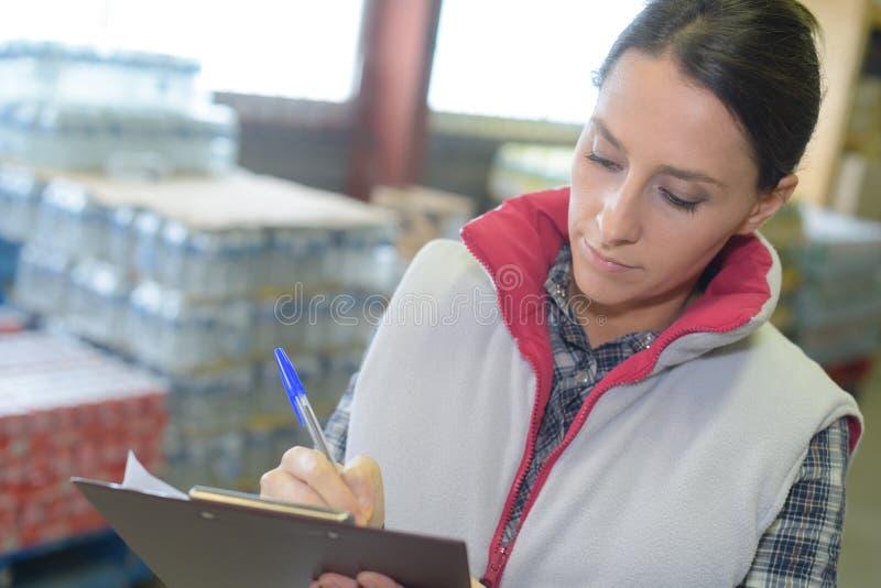 Skrivplatta och notera för kvinnlig fabriks- jobbare hållande royaltyfri bild