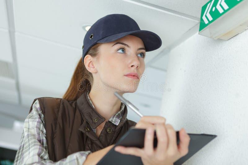 Skrivplatta och notera för kvinnlig fabriks- jobbare hållande fotografering för bildbyråer