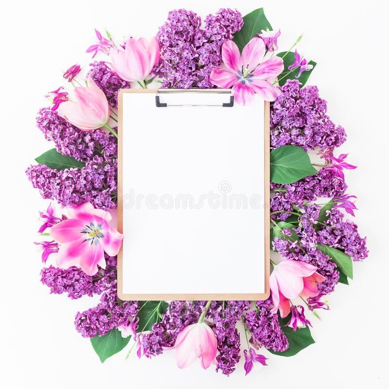 Skrivplatta, tulpan och lila filial på rosa bakgrund Lekmanna- lägenhet, bästa sikt Skönhetbloggbegrepp royaltyfri bild