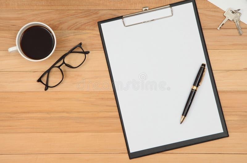 Skrivplattan med mellanrumet återanvänder papper, penna, glasögon och kaffe c royaltyfri bild