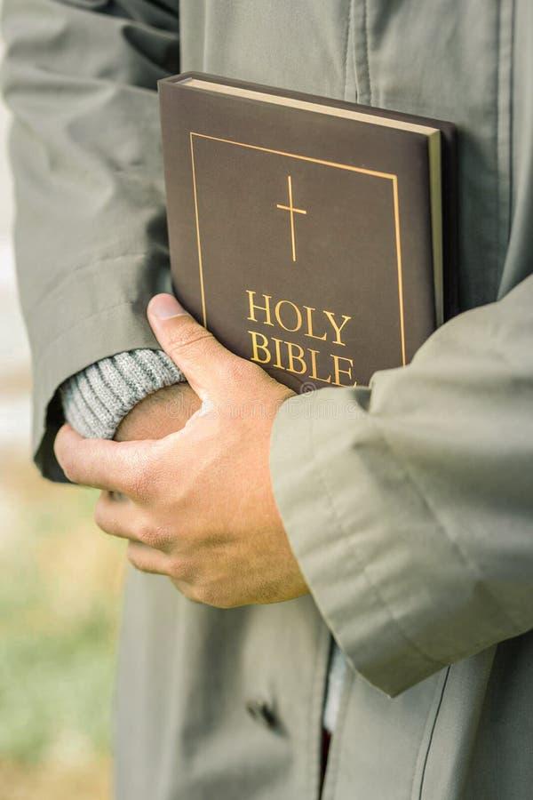 Skromnie mężczyzna ściśle trzyma hardcover biblię w jasnopopielatym żakiecie fotografia royalty free