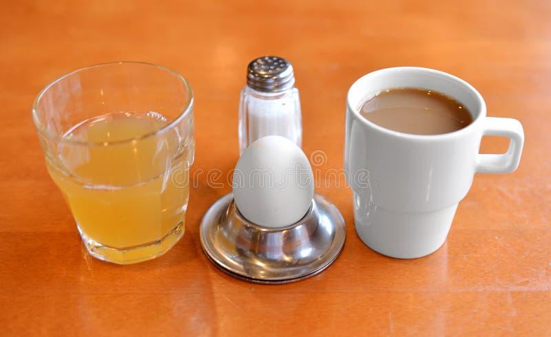 Skromny śniadaniowy jajko, sok, sól i kawa, zdjęcie stock