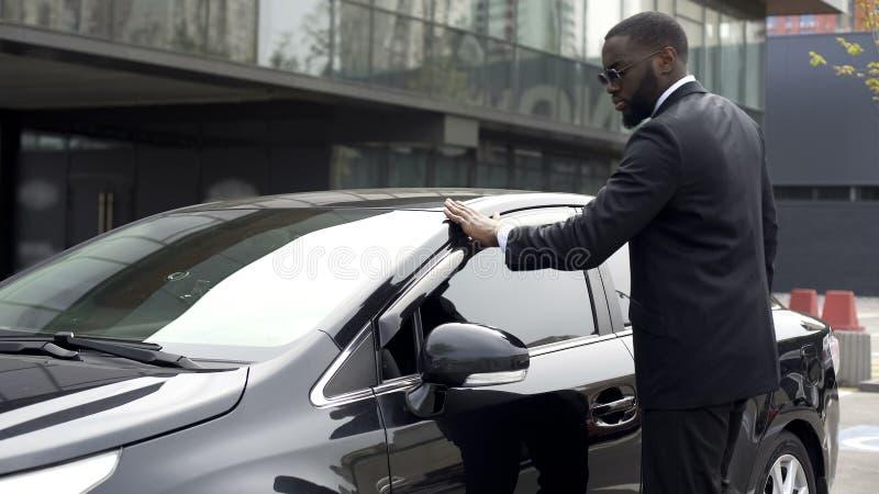 Skrupulatnie amerykanina mężczyzna wyciera jego nowego samochód przed opuszczać parking zdjęcie stock