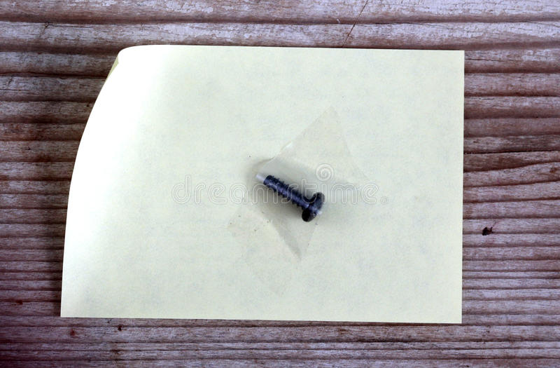 Skruva med fast med tejp på anmärkningspapper royaltyfri bild