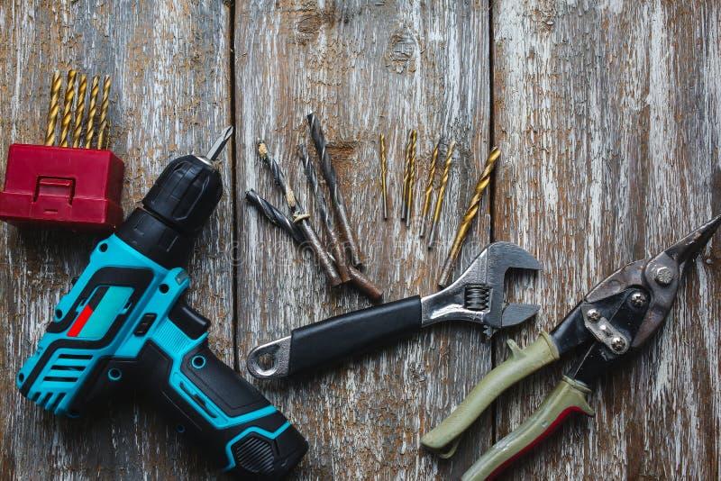 Skruva vapnet, skiftnyckeln, klipp, och metalldrillborren ligger på den gamla träbakgrunden Arbetande instrument på texturen för arkivbild