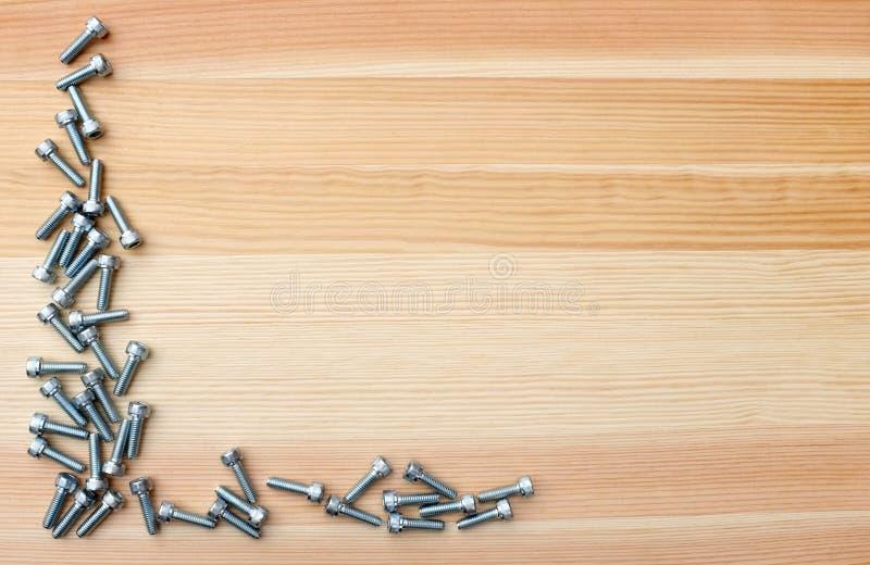 Skruvar för hålighethuvud som L-Shape gränsar på woodgrainbakgrund arkivfoto