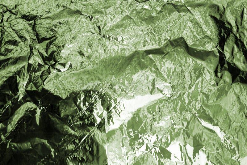 Skrynklig grön folie texturerad bakgrund, abstrakt illustration för bästa sikt för berglandskap, kaki- kamouflagefärgmodell fotografering för bildbyråer