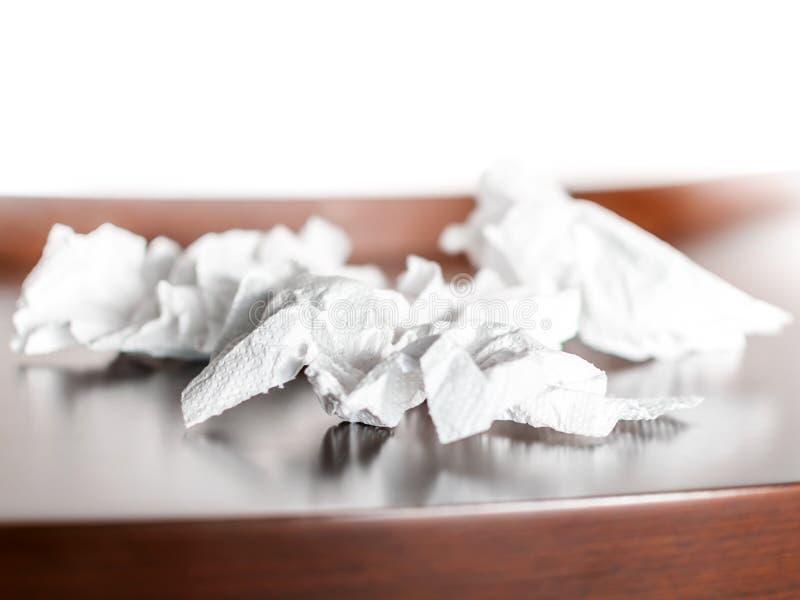 Skrynkliga papper eller servetter för närbild vit på en brun tabellbakgrund fotografering för bildbyråer