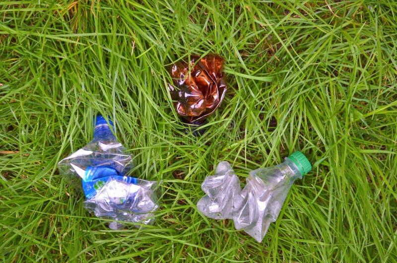Skrynkliga plast- flaskor ligger på gräset, avskräde i gräset royaltyfri foto
