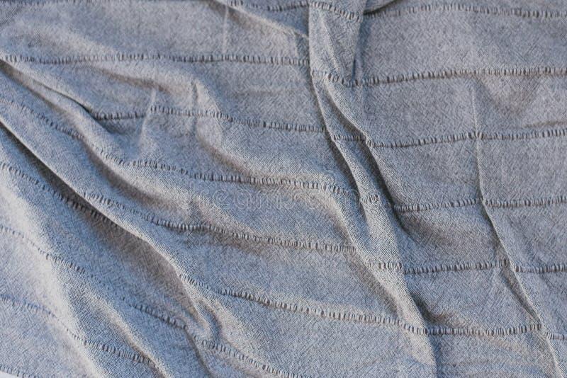 skrynkligt grått tyg veck på en grå överkast Textur av skrynkligt tyg royaltyfri bild