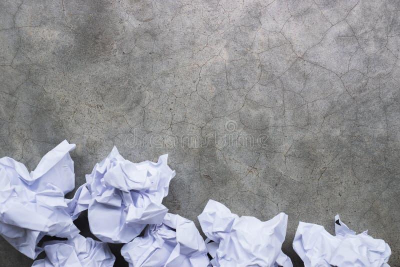 Skrynkligt papper klumpa ihop sig på en grå konkret yttersida royaltyfria foton
