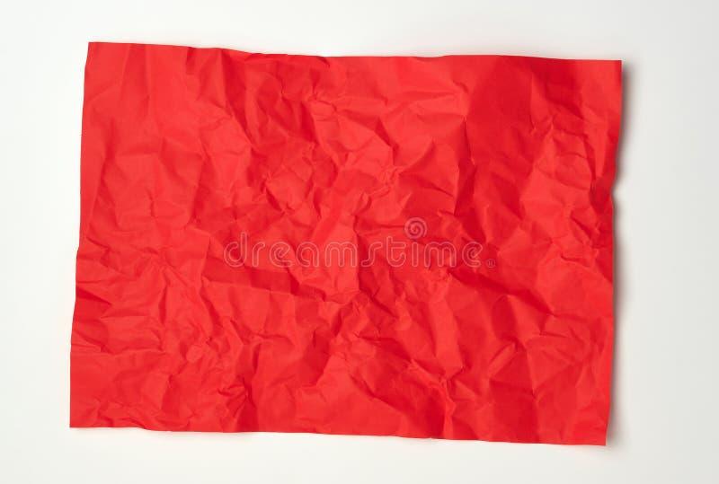 skrynkligt rött rektangulärt ark av papper på en vit bakgrund royaltyfria foton