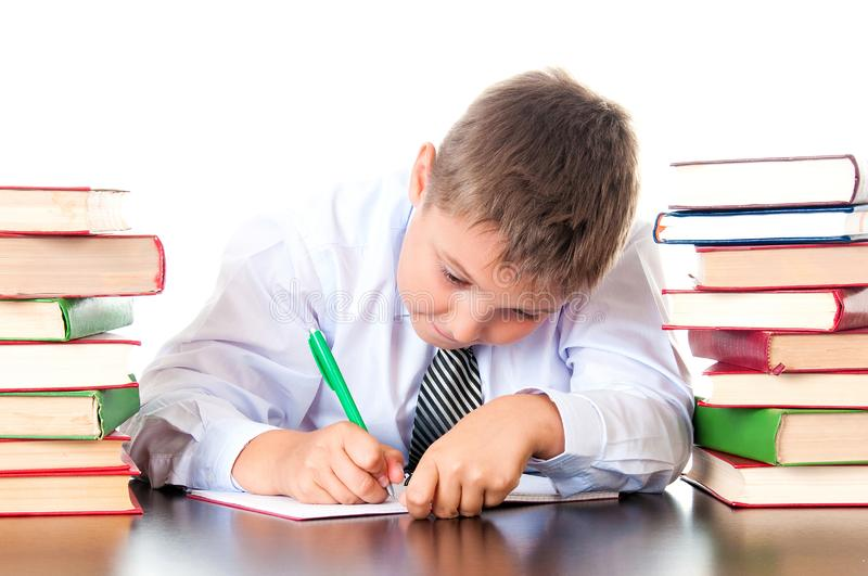 Skrzętnej szkoły średniej studencka chłopiec siedzi w bibliotece z książkami i uczy się lekcje, pisze pracie domowej Egzaminu prz fotografia royalty free