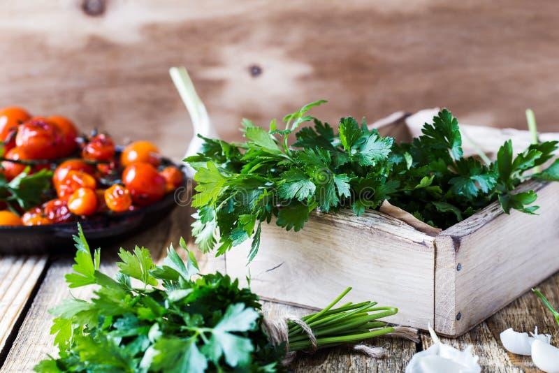 Skrzynka świeżo ukradziona organicznie pietruszka, piec czereśniowi pomidory i świeży czosnek na wieśniaka stole, obrazy stock