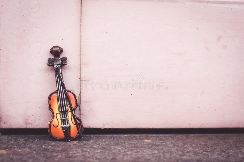 skrzypce miniatura nad drewnianą ścianą z retro koloru brzmieniem odbitkowa przestrzeń na dobrze dla teksta obraz stock