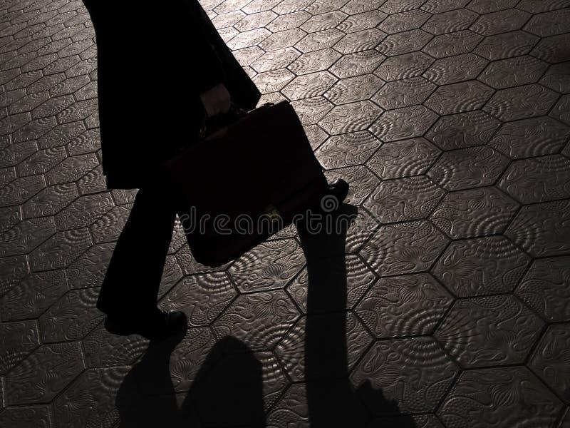 Skugga av affärsmannen som går med portföljen arkivfoto