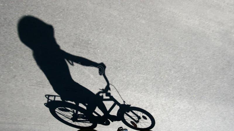 Skugga av barn på en cykel