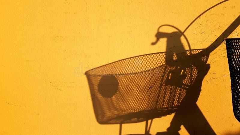 Skugga av en cykel på den livliga gula väggen arkivbilder