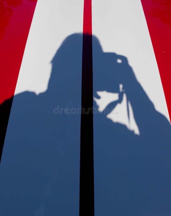 Skugga av en fotograf på en bil arkivbilder