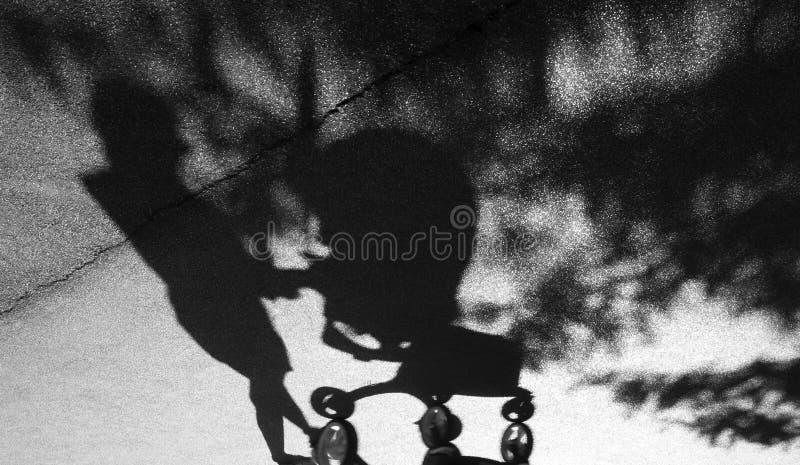Skugga av en kvinna som skjuter en behandla som ett barnspårvagn royaltyfri fotografi