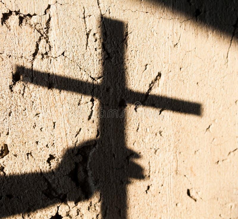 Skugga av handen som rymmer ett kors arkivfoto