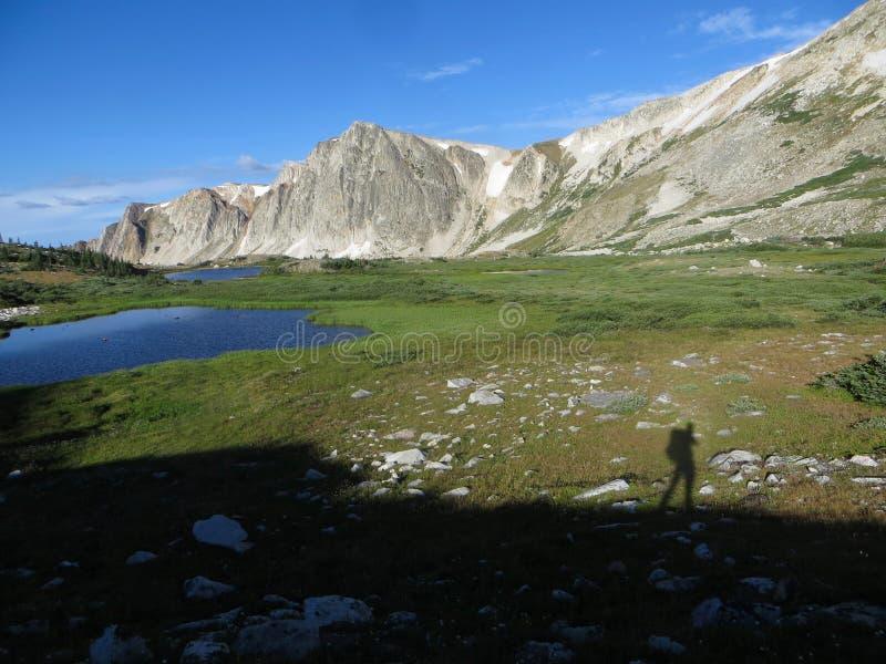 Skugga av solo en fotvandrare i bergen arkivfoton
