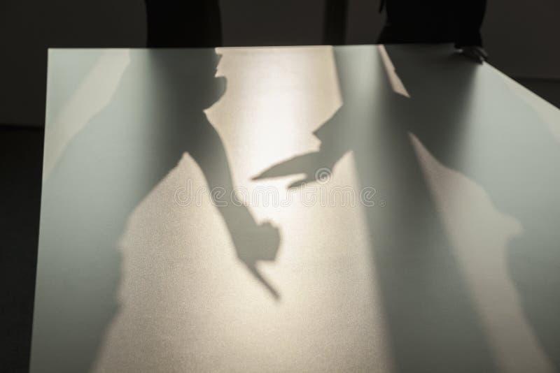 Skugga av två affärspersoner som argumenterar och gör en gest på golvet av kontoret arkivbild