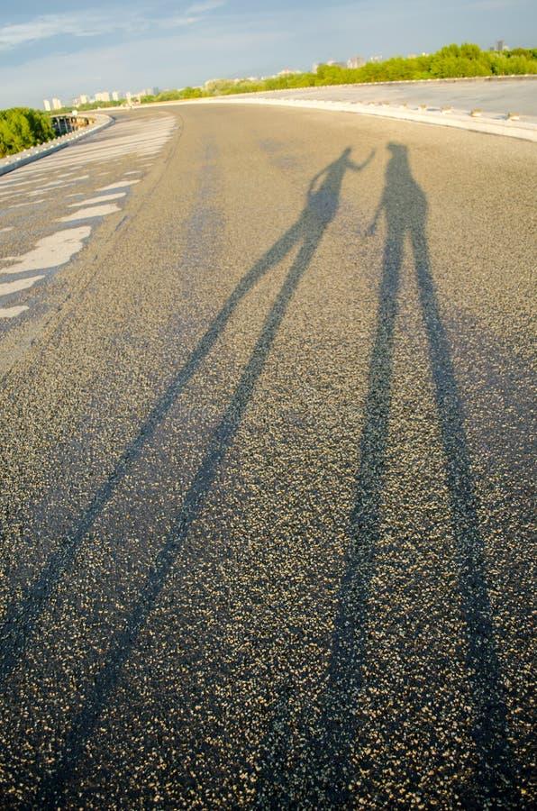 Skugga av två konstiga personer på vägen arkivbild