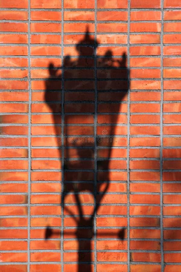 Skugga för gatalampa på en vägg för röd tegelsten arkivfoto