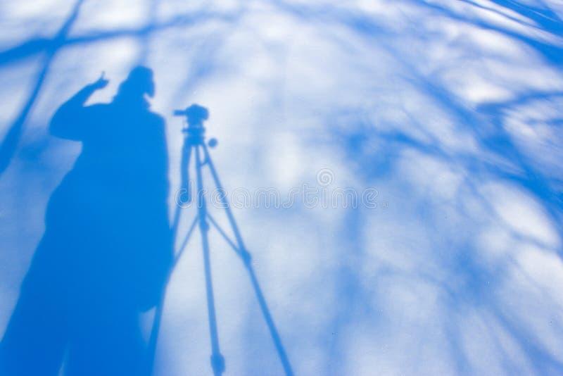 Skugga fotografen med en tripod i snön royaltyfri foto