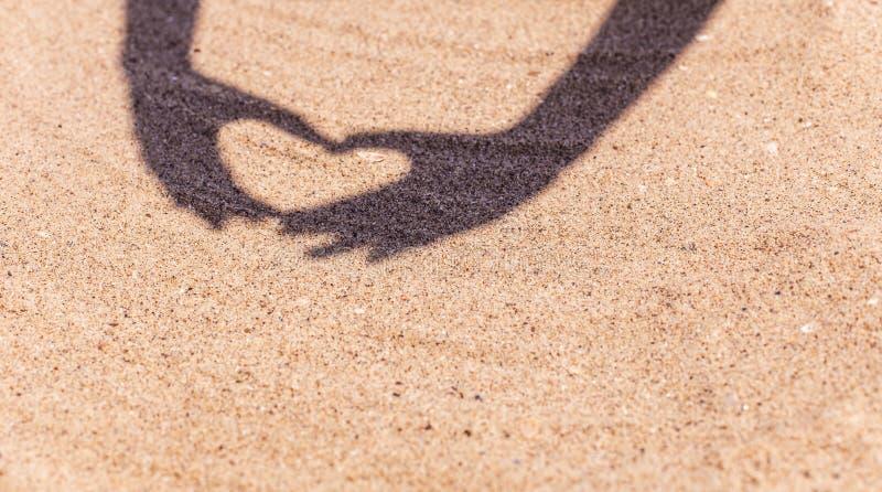 Skugga från händer i formen av hjärta på sanden på stranden med utrymme för texten Havslopp och ferie royaltyfri bild