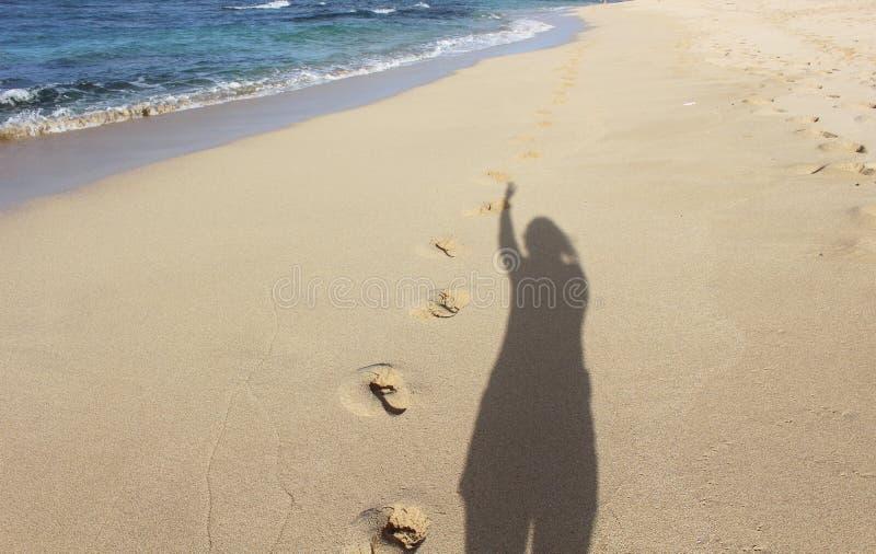 Skugga och fotspår på en strand royaltyfri fotografi