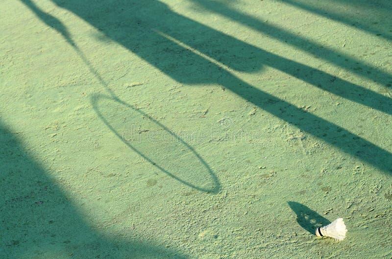 Skugga på jordningen med badmintonracket och gammal fjäderboll arkivfoton