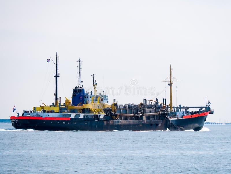 Skugga sughopperdredgeren sänd avlastning på Nordsjön nära royaltyfri fotografi