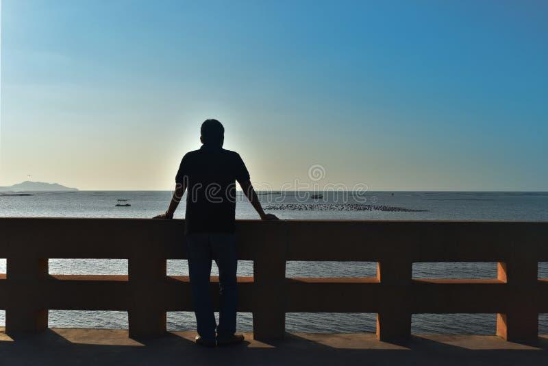 Skuggabaksidan av den asia mannen 40 gamla år framdelen är havet arkivfoto