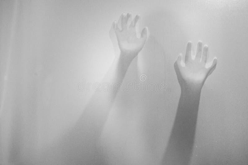 Skuggahänder av kvinnan bak frostat exponeringsglas Oskarp handabstr royaltyfri bild