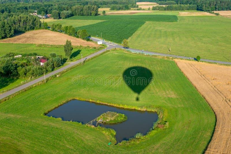 Skuggan av en ballong för varm luft som flyger över fält och ängar fotografering för bildbyråer
