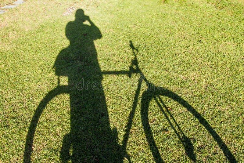 Skuggan av en cykel och ett folk på den gröna färgen för gräs som bakgrunden arkivbild