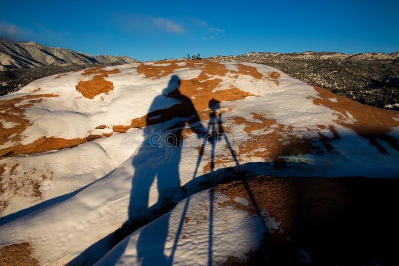Skuggan av en fotograf, en kamera och en tripod på den täckte snön vaggar av trädgården av gudarna parkerar royaltyfria foton