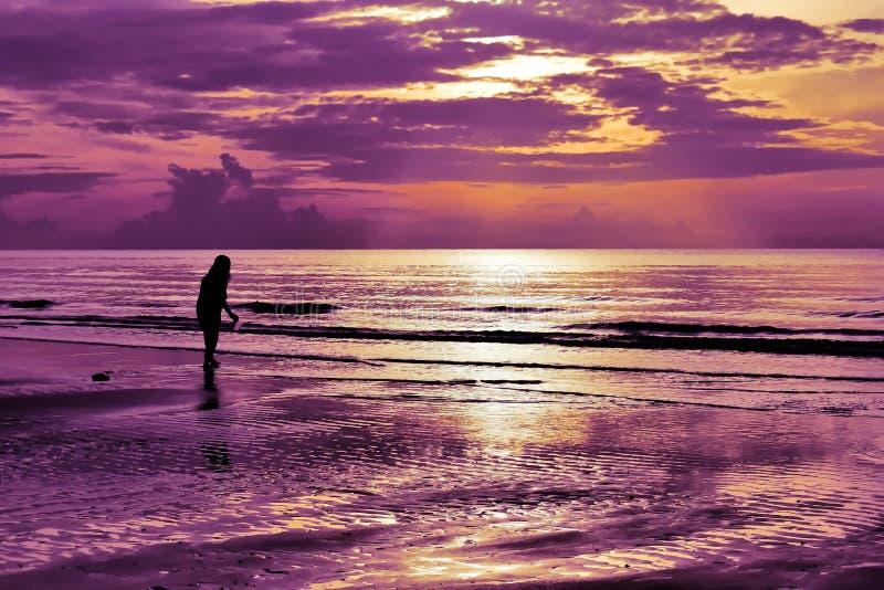 Skuggan av en kvinna som går på stranden på soluppgång royaltyfri bild