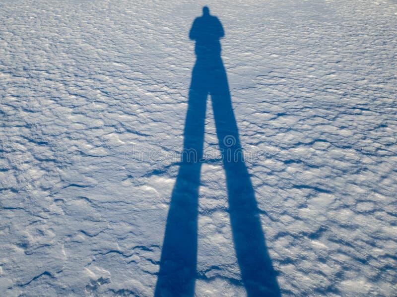 Skuggan av en man i sn?n arkivfoto