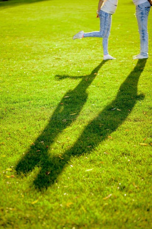 Skuggan av ett ungt par på gräset royaltyfri bild
