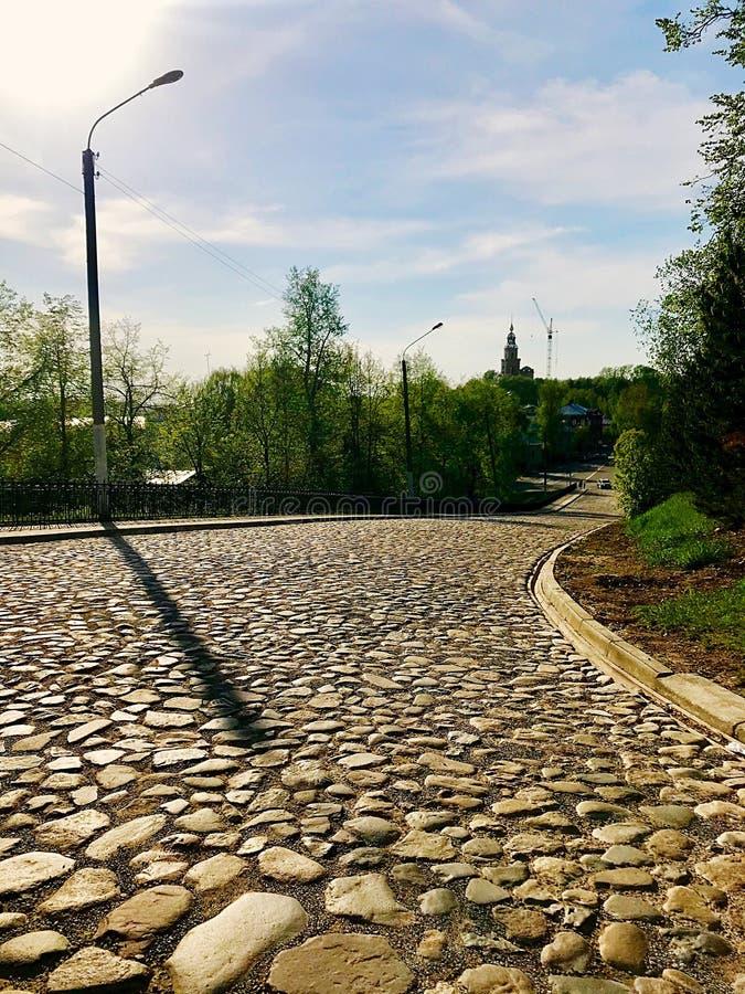 Skuggan av pelaren på vägen som fodras med stenar royaltyfria foton