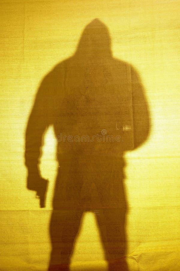 Skuggan bak tyg av en man med ett vapen royaltyfri foto