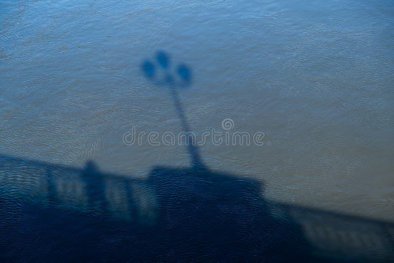 Skuggan på vattnet av ett mananseende på en bro bredvid ledstången royaltyfri fotografi