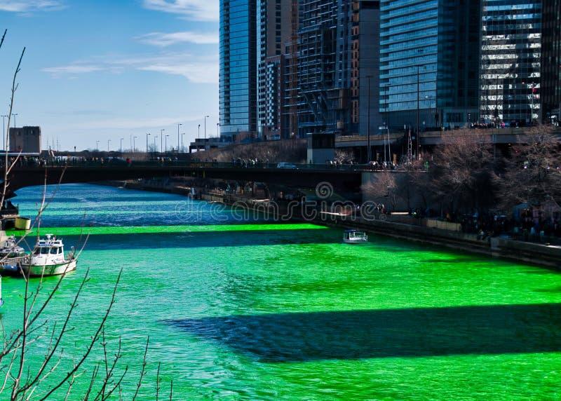 Skuggar av byggnader som gjutas längs Chicagoet River som är färgad gräsplan för dag för St Patrick ` s arkivfoto